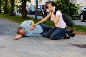 Medical Emergency_Woman on Phone with Man in Recovery Position